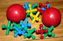 Picture of two red rubber balls and various colored plastic jacks pieces